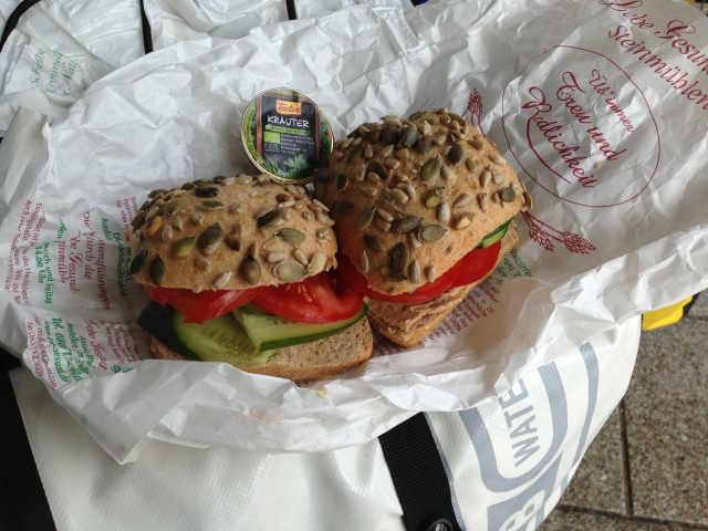 A common lunch on the go, in this case prepared on the back of my bike while on a train platform: tomatoes and cukes on a pumpkin-seed roll with Tartex spread.